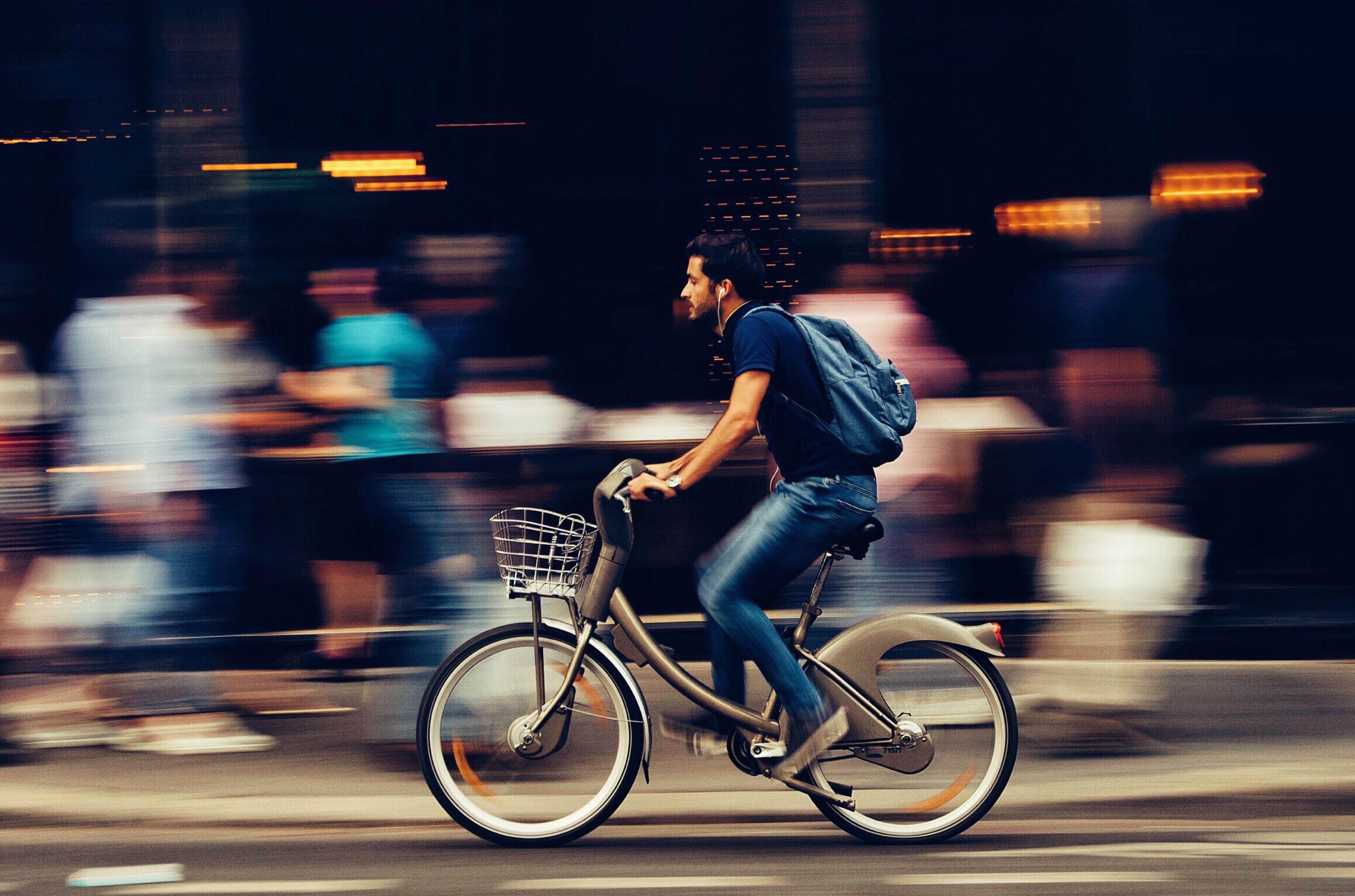 Mann som sykler i byen